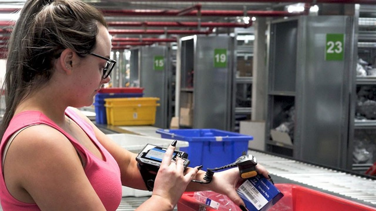 Worker on manufacturing line using Zebra multi\u002Dmodal voice solutions