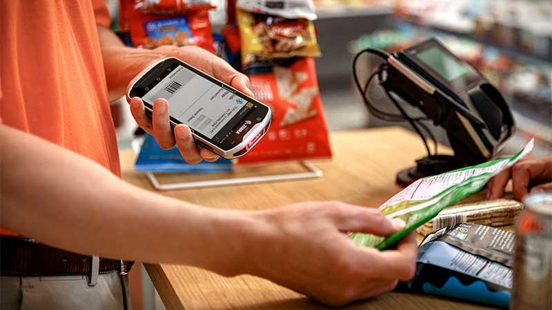 Employee scanning a bag of snacks at the checkout counter.