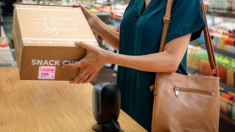 Retail customer scanning a box in a convenience store.