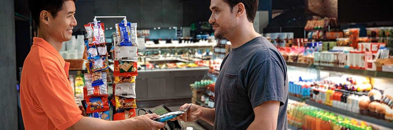 Man buying items in a convenience store from a clerk.