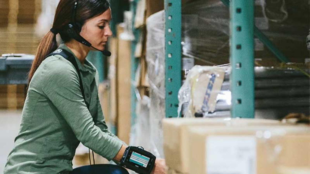 Woman scanning boxes in warehouse with zebra products