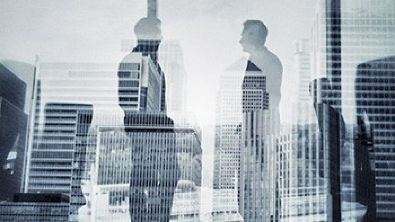 Reflection of two men talking in front of a window with a city skyline background