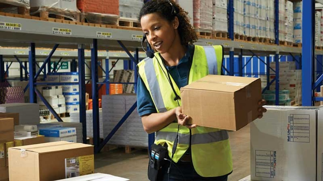 Woman wearing a Zebra device on her waist and moving boxes in a warehouse