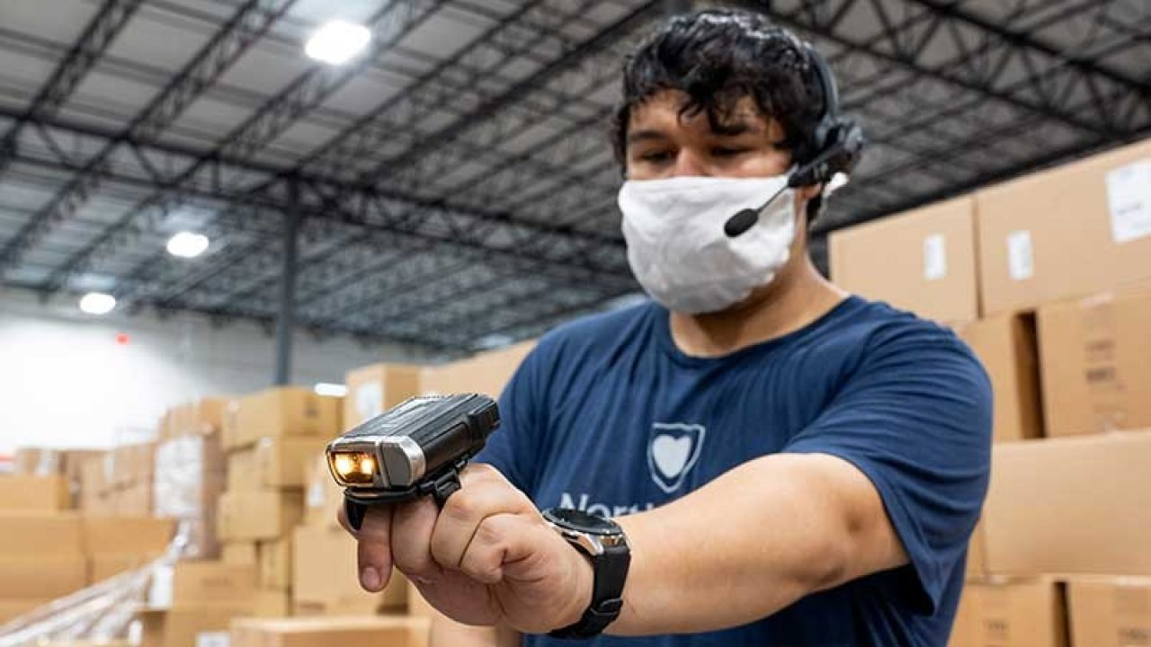 Masked warehouse employee with a ring scanner and headset