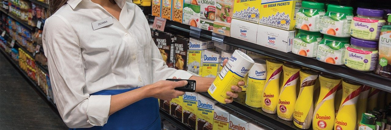 Grocer using scanner to track products of shelves
