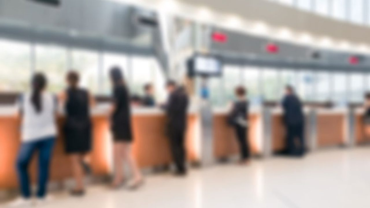 Blurred image of people standing at counter in a bank